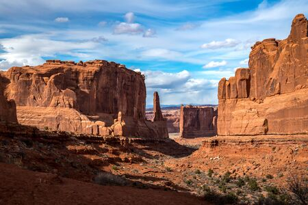 Scenic view of monolithic sandstone rock structures seen along the Park Avenue Trail with Tower of Babel in the distance, Arches National Park, Moab, Utah