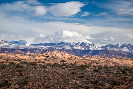 Stunning view of the remnants of ancient sand dunes in the high desert with snowcapped La Sal Mountains in the background, Arches National Park, Moab, Utah