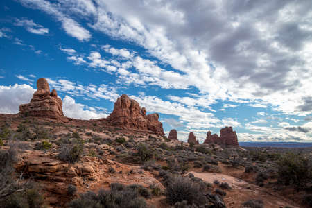Beautiful cloudscape over Turret Arch and surrounding sandstone rock formations on a sunny day, Arches National Park, Moab, Utah