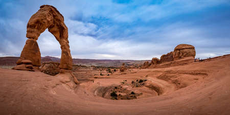 Iconic Delicate Arch landmark standing tall in the Arches National Park on a cloudy day with La Sal Mountains in the background, Moab, Utah