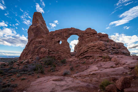 Beautiful Turret Arch rock formation backlit by the sun and dramatic clouds in the sky, Arches National Park, Moab, Utah