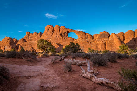 Bright sunlight illuminating the beautiful Skyline Arch sandstone rock formation at golden hour, Arches National Park, Moab, Utah