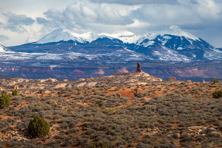 Single sandstone rock formation in the high desert with snowcapped La Sal Mountains in the background, Arches National Park, Moab, Utah