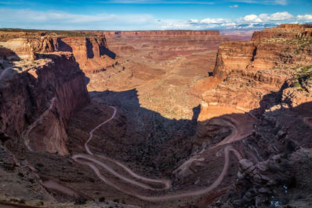 Breathtaking view of rugged Shafer Trail winding down into Shafer Canyon on a sunny day,  Shafer Trail Viewpoint, Island in the Sky District, Canyonlands National Park, Moab, Utah