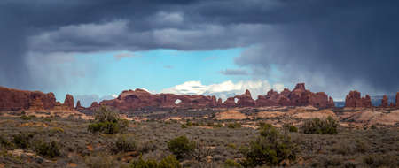 Beautiful sandstone rock formations with dramatic storm clouds looming in the distance, Arches Scenic Drive, Arches National Park, Moab, Utah 版權商用圖片