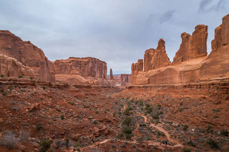 Massive sandstone rock towers in the Park Avenue Trail of Arches National Park with dramatic storm clouds looming overhead, Moab, Utah 版權商用圖片
