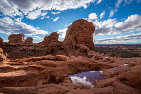 Gorgeous view atop of Turret Arch surrounded by tall sandstone spires and puddles of water that reflect the cloudy blue sky, Arches National Park, Moab, Utah