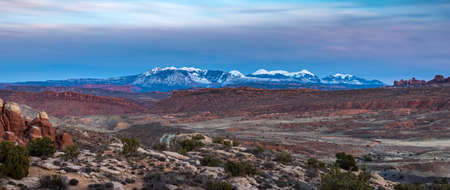 Long shadows cast across the beautiful landscape of Arches National Park at sunset with the red cliffs of Fiery Furnace in the foreground and La Sal Mountains in the distance, Moab, Utah