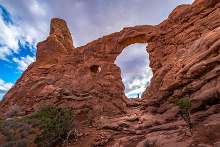 Low angle view of Turret Arch with a person standing in the giant window, Arches National Park, Moab, Utah 版權商用圖片