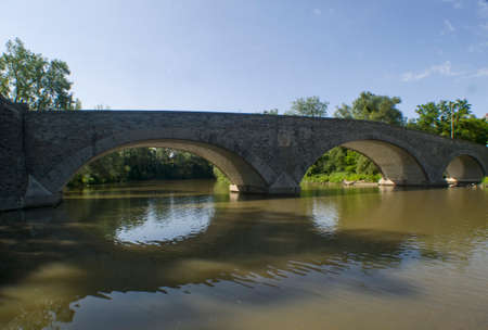 stone arched bridge over river wide shot