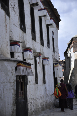 Tibetan monk and villagers walking by the alley