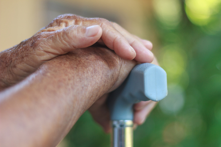people with disabilities: Closeup old hand with crutch Stock Photo