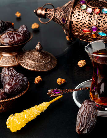 Ramadan concept with cup of tea and dried dates.