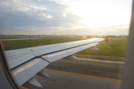 taking off: Airplane wing while taking off with sunrise Stock Photo