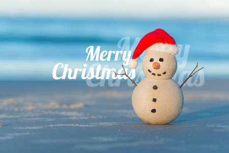 Sandy Christmas Snowman on a beautiful beach with Merry Christmas wishes