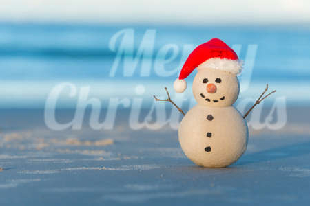 Sandy Christmas Snowman on a beautiful beach in sunset with Merry Christmas wishes in the background