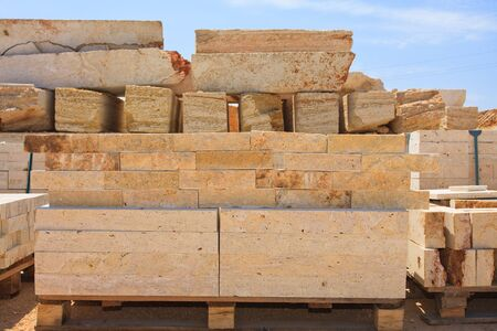 l natural: blocks of limestone processed and ready for use, are against the blue sky