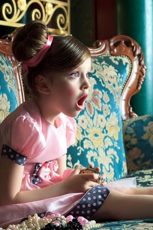 occhi sbarrati: Sorpreso ragazza si siede con gli occhi aperti e la bocca