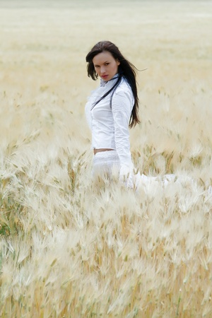 Sexy, young woman dancing in a field of wheat photo