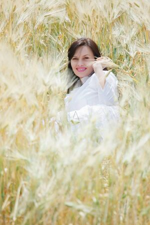 Young sexy woman lying in a field of rye, happy, smiling and having fun  photo