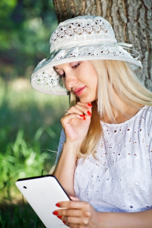 Beautiful girl is reading news and watching photos with photo