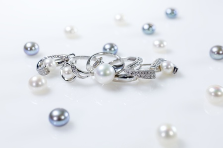 A set of two rings and earrings with pearls  Objects lying on a white table surrounded by pearls of different colors  photo