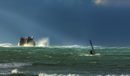 A surfer rides the storm, near the sunken ship