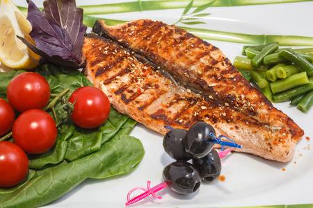 pesce cotto: pesce cucinato e verdure fresche sul piatto Archivio Fotografico