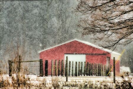 Snow Falling On Red Barn With Fence