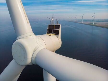 close view with drone at windmill park in the lake Ijsselmeer in the netherlands Noordoostpolder, Windmill turbines from above in Europe producing green energy Stock Photo