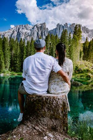 couple visit hte bleu lake in the dolomites Italy, Carezza lake Lago di Carezza, Karersee with Mount Latemar, Bolzano province, South tyrol, Italy. Landscape of Lake Carezza or Karersee and Dolomites in background, Nova Levante, Bolzano, Italy. Europe Reklamní fotografie