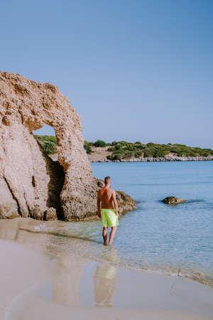 Tropical beach of Voulisma beach, Istron, Crete, Greece ,Most beautiful beaches of Crete island -Istron bay near Agios Nikolaos , young guy mid age on vacation Crete at the beach