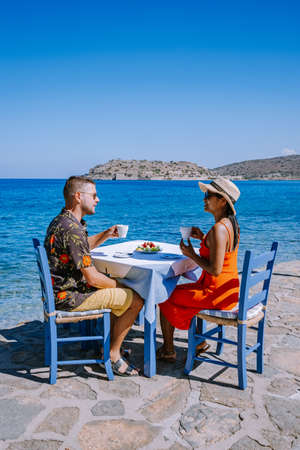 Crete Greece Plaka Lassithi with is traditional blue table and chairs and the beach in Crete Greece. Paralia Plakas, Plaka village Crete, couple on vacation holiday in Greece 版權商用圖片
