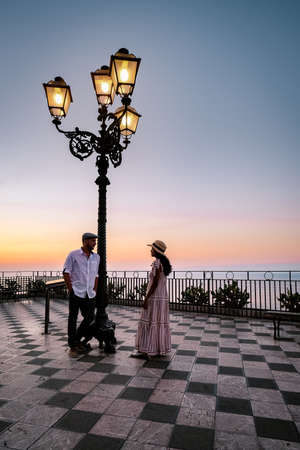Taormina Sicily, couple men and woman mid-age watching the sunrise at the old town of Taormina Sicilia Italy Stock Photo