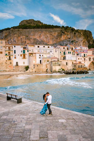 couple on vacation Sicily visiting the old town of Cefalu,sunset at the beach of Cefalu Sicily, old town of Cefalu Sicilia panoramic view at the colorful village.Italy