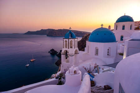 Sunset at the Island Of Santorini Greece, beautiful whitewashed village Oia with church and windmill during sunset, streets of Oia Santorini during summer vacation at the Greek Island Standard-Bild