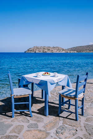 Crete Greece Plaka Lassithi with is traditional blue table and chairs and the beach in Crete Greece. Paralia Plakas, Plaka village Crete Standard-Bild