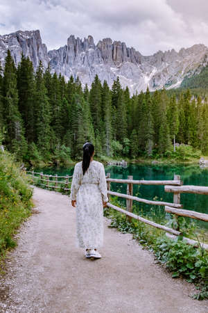 woman visit bleu lake in the dolomites Italy, Carezza lake Lago di Carezza, Karersee with Mount Latemar, province, South tyrol, Italy. Landscape of Lake Carezza or Karersee and Dolomites in background, Nova Levante, , Italy. Europe