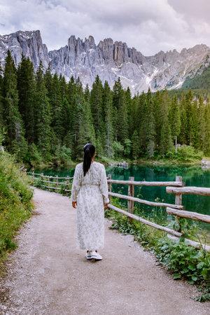 woman visit bleu lake in the dolomites Italy, Carezza lake Lago di Carezza, Karersee with Mount Latemar, Bolzano province, South tyrol, Italy. Landscape of Lake Carezza or Karersee and Dolomites in background, Nova Levante, Bolzano, Italy. Europe Reklamní fotografie
