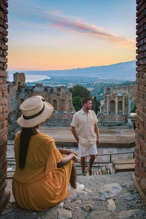 Taormina Sicily, couple watching sunset at the Ruins of the Ancient Greek Theater in Taormina, Sicily. couple mid age on vacation Sicilia 写真素材