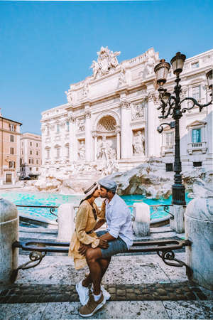 young couple mid age on a city trip in Rome Italy Europe, couple sightseeing visit Fontana di Trevi in Rome Italy