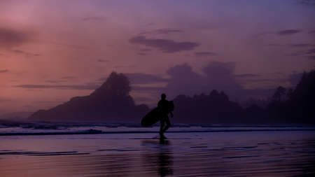 Vancouver Island Tofino, sunset at the beach with surfers in the ocean, beautiful colorful sunset with pink and purple colors in the sky at Vancouver Island with people surfing. Canada