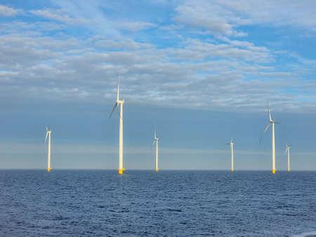Windmill village indrustial wind mill by the lake Ijsselmeer Nehterlands. renewable energy green energy