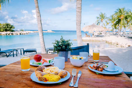 breakfast on a table by the beach looking out over the ocean, Caribbean sea with breakfast table with coffee orange juice and croissants and fruit. bright scenery sunny day beach