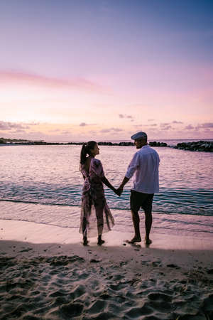 Curacao Willemstad, couple mid age Asian woman and European man on vacation at a luxury resort in Pietermaai , men and woman on the beach watching sunrise with beautiful orange pink sky Foto de archivo