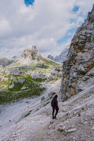 Tre Cime di Lavaredo peaks or Drei Zinnen at sunset, Dobbiaco Toblach, Trentino -Alto Adige or South Tyrol, Italy. Europe Alps. Asian woman hiking in the mountains