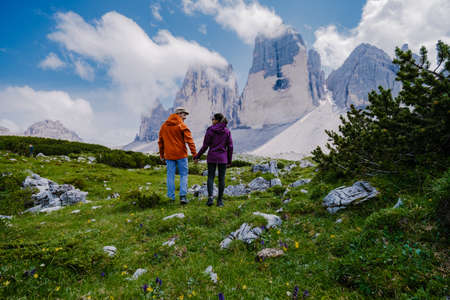 Tre Cime di Lavaredo peaks or Drei Zinnen at sunset, Dobbiaco Toblach, Trentino -Alto Adige or South Tyrol, Italy. Europe Alps. couple man and woman hiking in the Dolomites