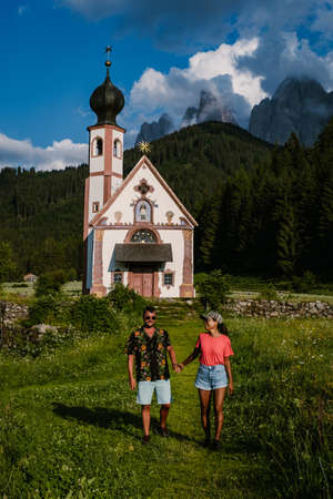 Santa Maddalena church village in front of the Geisler, Val di Funes, Italy, Europe. couple mid age man and woman on vacation in Italy, Asian woman, caucasian man, Alpine church Ranui, Santa Maddalena