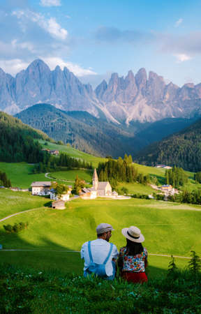 Santa Magdalena village in Val di Funes on the italian Dolomites. Autumnal view of the valley with colorful trees and Odle mountain group. Italy, man and woman on vacation, hiking in the mountains