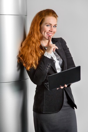 communicative: girl in the office with a laptop in the hands of his finger to his mouth Stock Photo